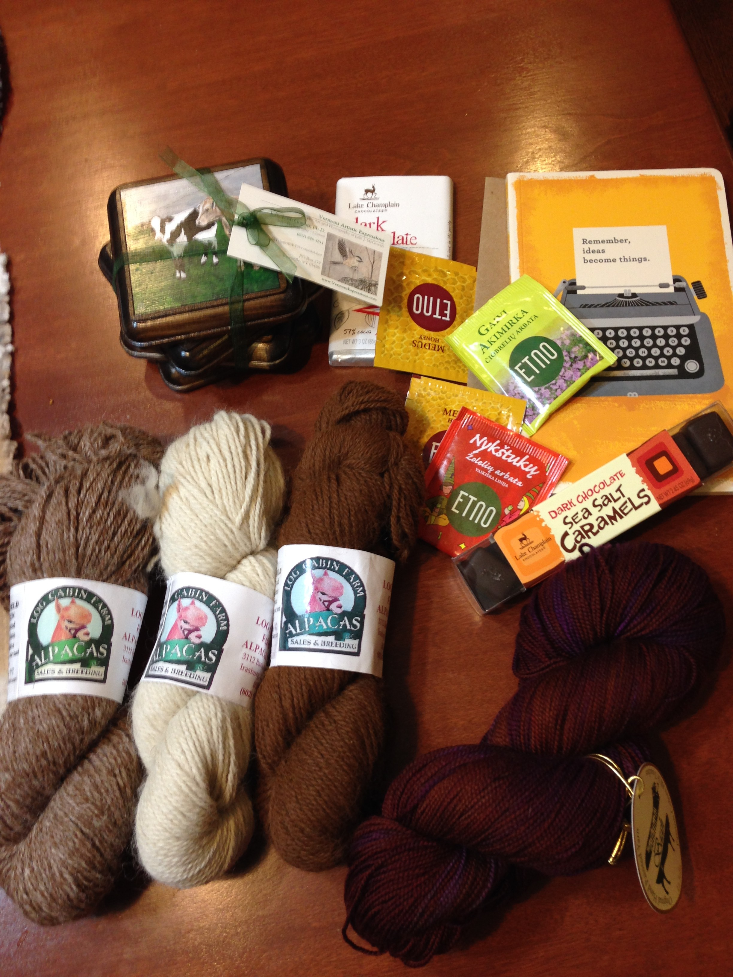 Clockwise from bottom left: Vermont alpaca, hand-painted coasters, Lithuanian chocolate and tea, a journal, and yummy sock yarn!