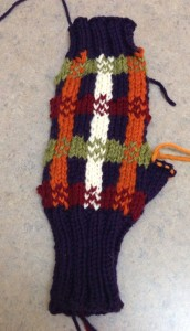 From the RS, but unblocked, no ends buried, right off the needles.  Thumb sts are on a piece of yarn, waiting to be picked up to knit the thumb.  Notice the really loose sts on the top row, in orange - where the yarn isn't settled.  Everywhere else the yarn has settled into place, although not secured.