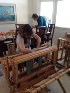 "I'm ""sleying the reed"", which means pulling the warp threads individually through the fixed slots in the reed.  Jen is behind me, working on the warp for her rigid heddle loom."