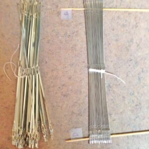 I found out, while threading, that I needed to redistribute heddles.  Ugh. I whittled bamboo skewers to hold them in place for the transfer.  The pieces of tape keep them from sliding off, and I write the number of heddles on the tape.