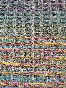 This is a waffle weave pattern for 4 shaft loom, from Davison book, page 57. I'm using stash yarn to play with colors and texture with the pattern. There is sock yarn - doubled - on top, some sparkly worsted in the middle, and the same worsted with ribbon on treadle rows 2 and 3 on the bottom.